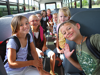 group of happy students on a school bus