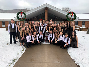 2019 Christmas Show students posing for a picture outside of school building