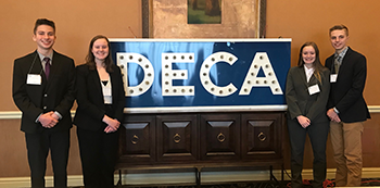 DECA state qualifiers pose together in front of a DECA sign