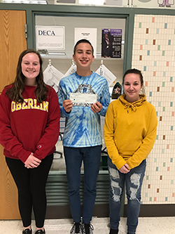 Three students pose with the check for the DECA donation