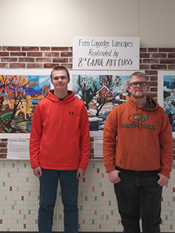 Oliver Johnson and Owen Holmberg pose together in front of a wall of art and a sign reading Fern Coppedge Landscapes Replicated by 8th Grade Art Class