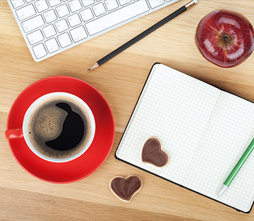 desk top with red coffee mug and notepad