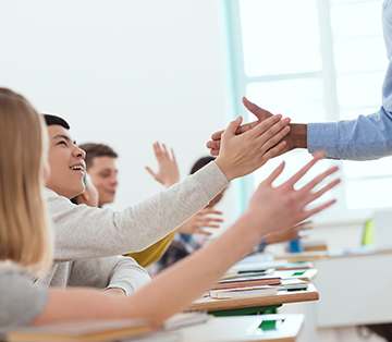 Teacher giving a student a high-five in the classroom