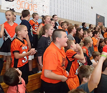 Students in sports jerseys, team attire and cheerleader outfits cheer at an event