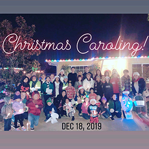 Christmas carolers pose outside of a house with text reading Christmas Caroling Dec 18, 2019