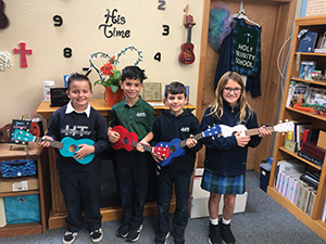 Four students pose with ukeleles in a classroom