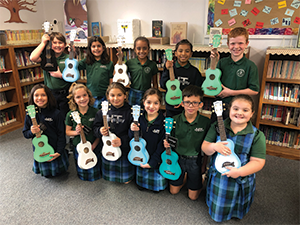 Eleven students pose with ukeleles in a classroom