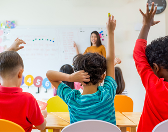 the back of students in a classroom with their hands raised