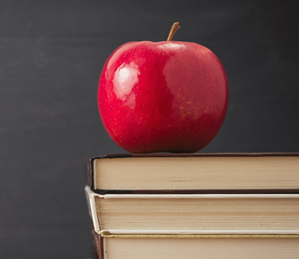 a red apple on a stack of books