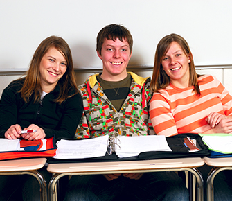 three students sitting in their desks smiling