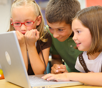 three students working together on a laptop