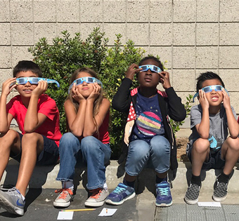 four students with sunglasses on watching the eclipse