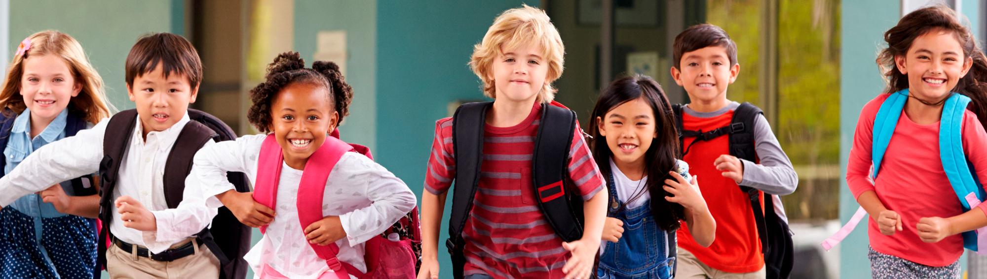 students wearing backpacks, running