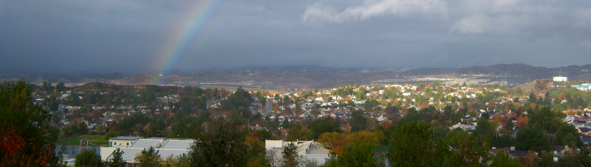 view of the town with a rainbow in the sky