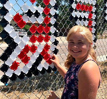 smiling girl decorating a fence
