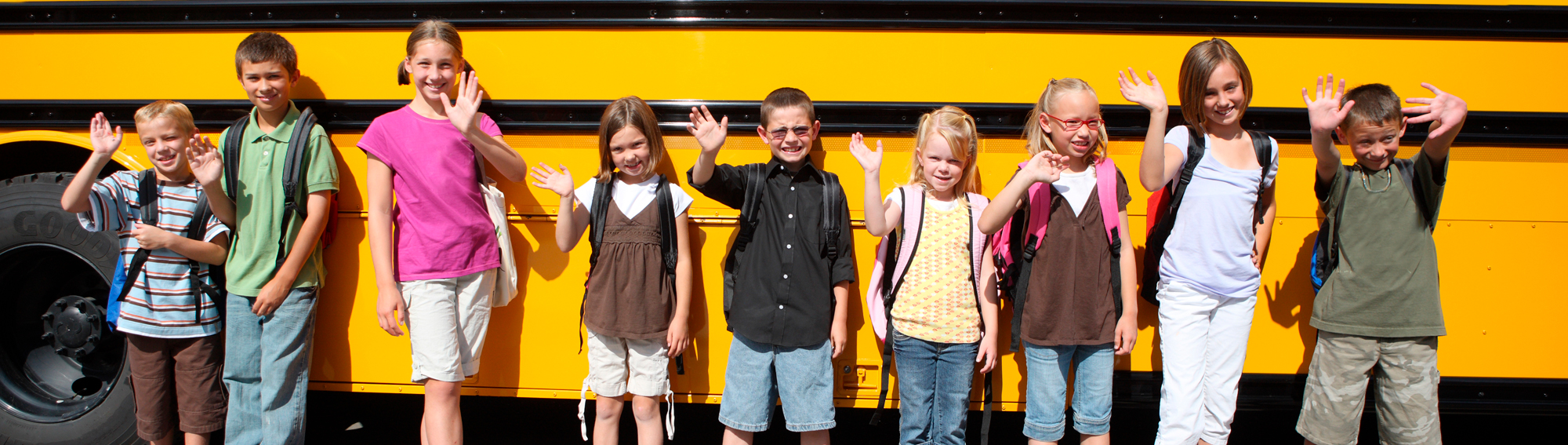 students standing in front of a bus waving