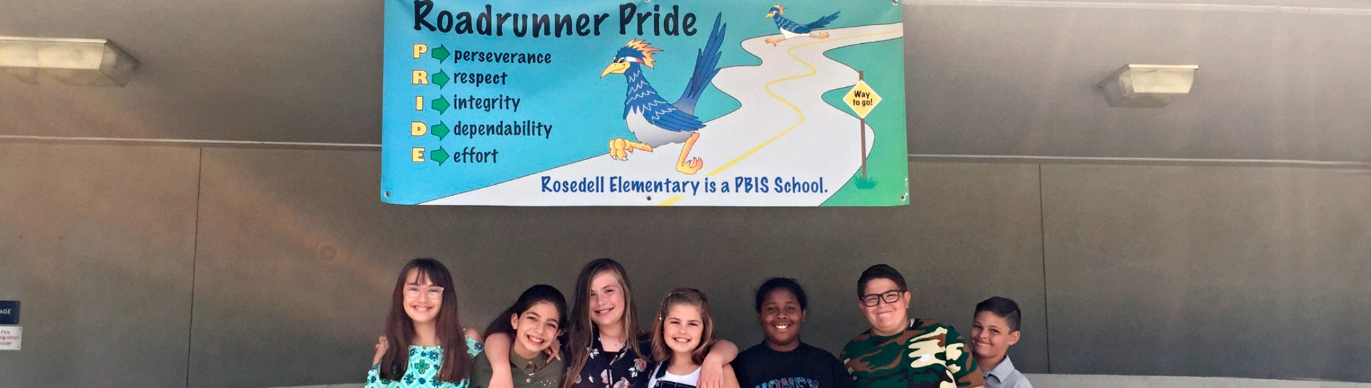 smiling students with a banner that says Roadrunner Pride. Perseverance, Respect, Integrity, Dependability, Effort. Rosedell Elementary is a PBIS School