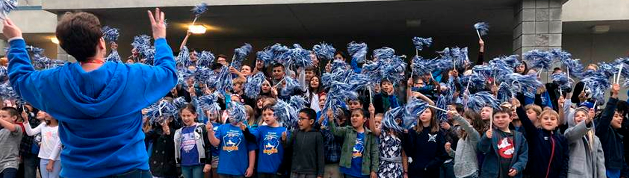 students and staff cheering and waving pom poms