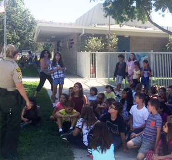 students and parents listening to an officer speak