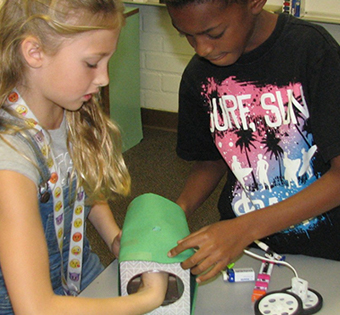 a boy and a girl working together on a project