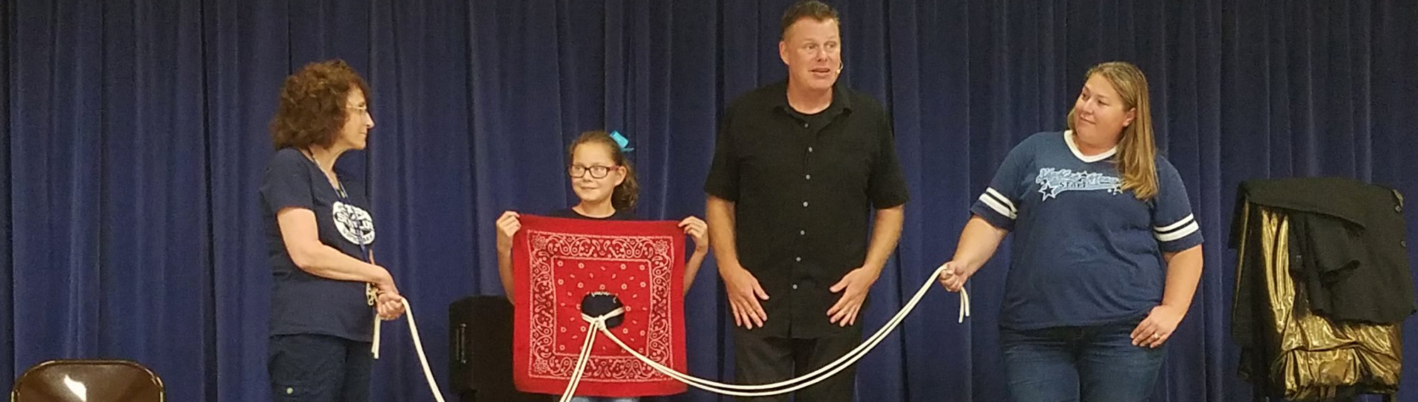 staff members holding a rope while a student is holding a handkerchief