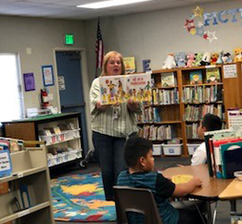 staff member reading to students in the library