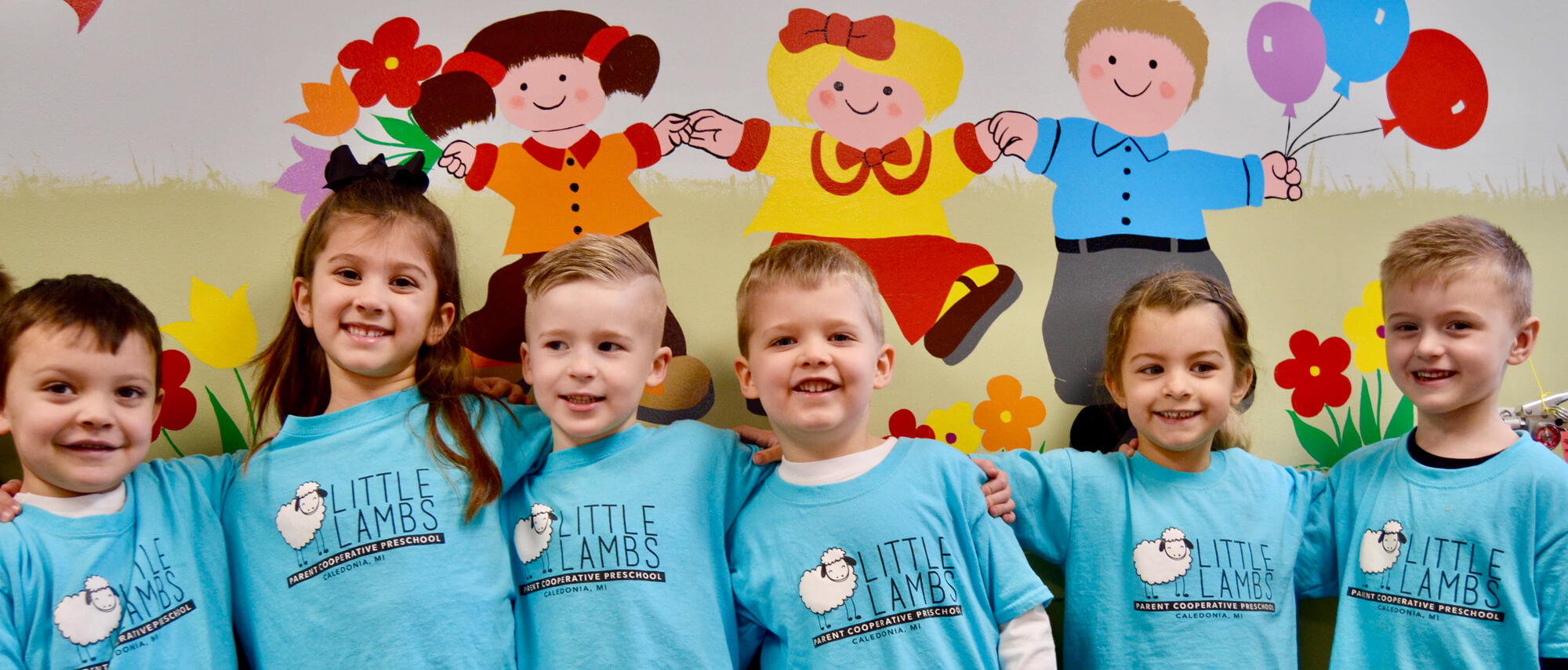Smiling children wearing Little Lamb tee shirts