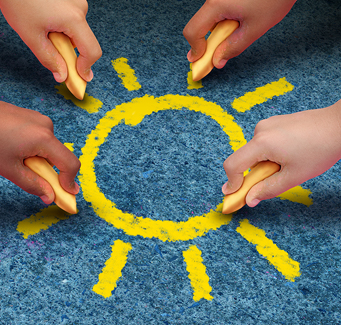 little hands drawing a sun with sidewalk chalk