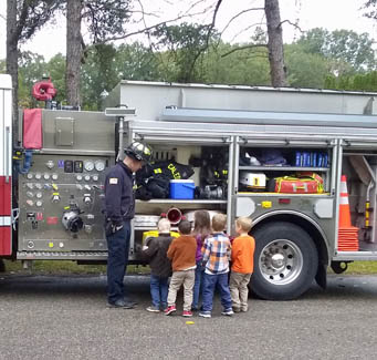 children looking at a fire truck