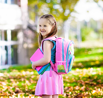 little girl wearing her backpack and carrying books