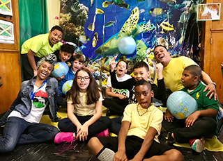 Students pose together with globes