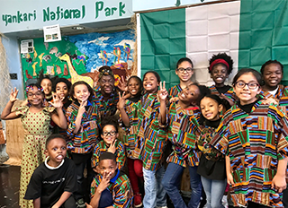 Group of students pose together in front of a Yankari National Park sign
