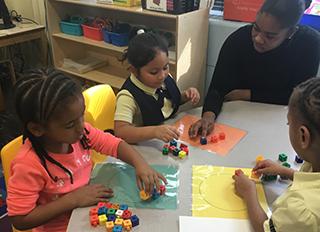 Teacher helps students using blocks