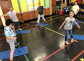 Students participate in an exercise activity using mats