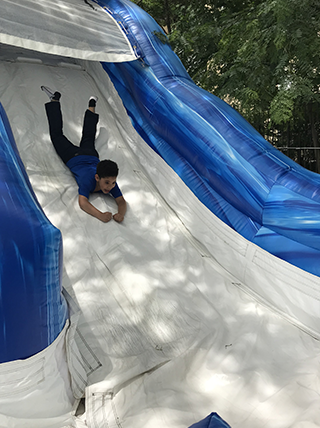 Male student sliding down an inflatable slide