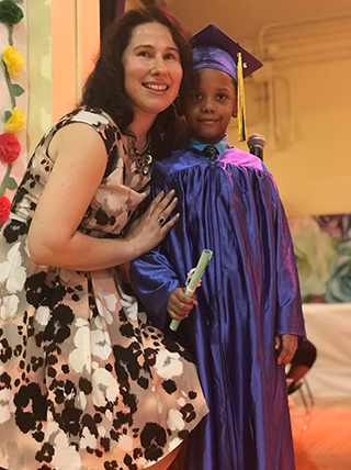 Staff member poses with a graduating student