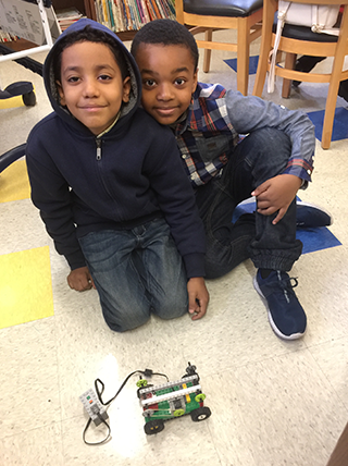 Two male students pose together with a Lego vehicle