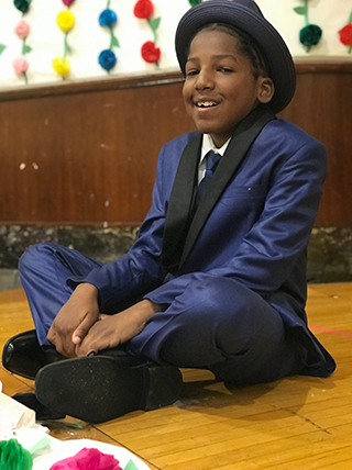 Smiling male student wearing fancy attire poses on the floor