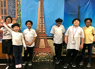 Students wearing French attire pose together next to a cut out of the Eiffel Tower