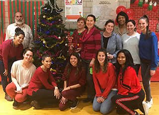 Staff members pose together in front of Christmas decorations