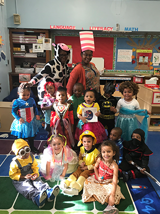 Staff members and students dressed as pop culture characters pose in a classroom