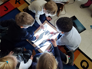 children looking at photo of hand