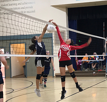 Female students playing volleyball against another school.