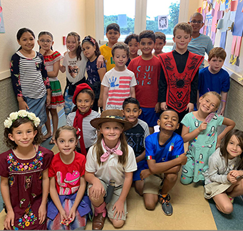 Many students dressed up in costumes in a hallway.