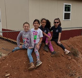 Four students sitting on a dirt pile.