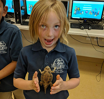 Female student standing with a bearded dragon on her chest.