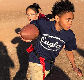 Male student playing flag football.
