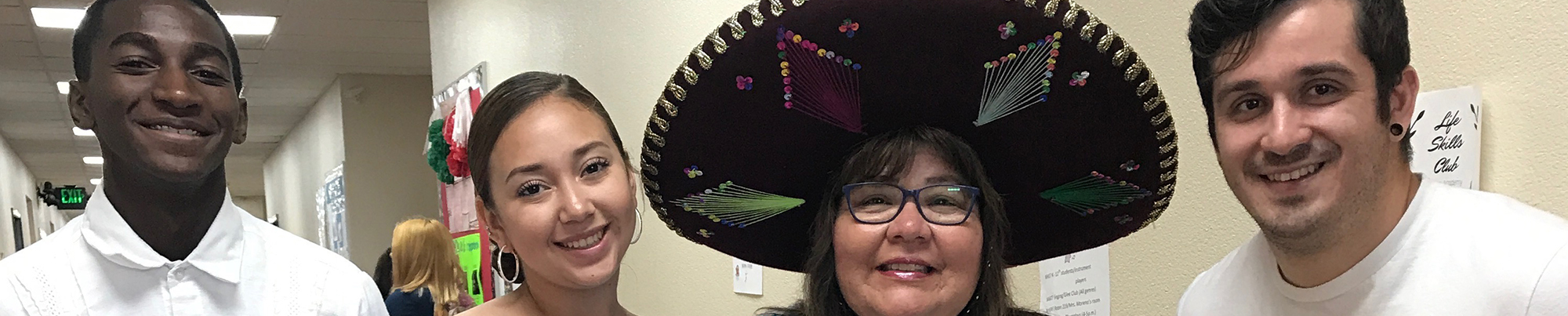 Four teachers smiling, one wearing a sombrero.