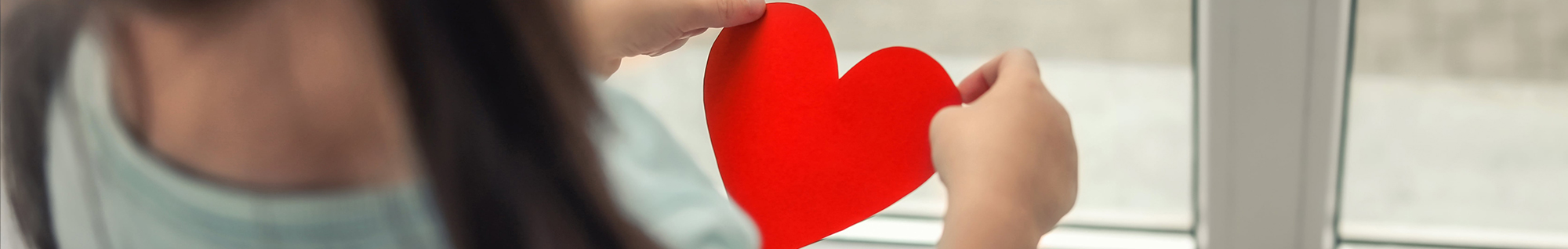 Little girl holding a red paper heart