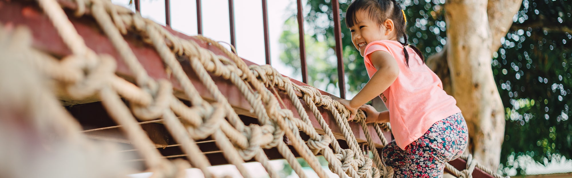 Happy little girl climbing a jungle gym rope
